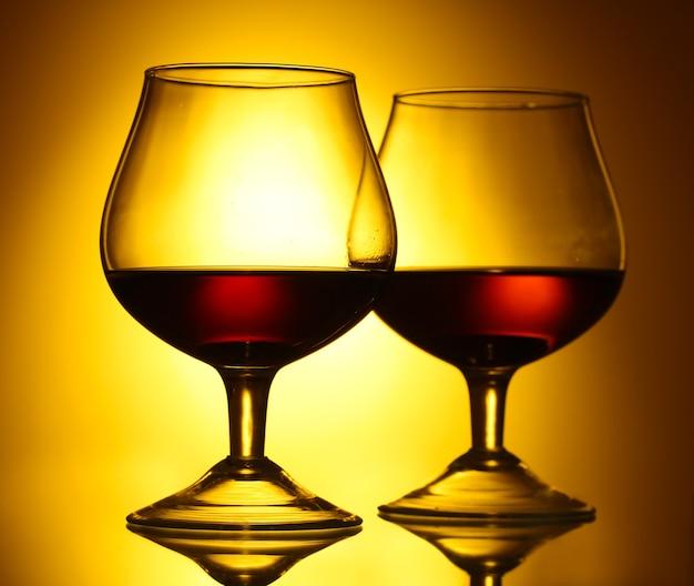 Dwie szklanki koniaku na żółtej przestrzeni
