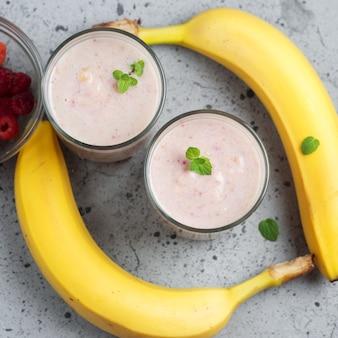 Dwie szklanki letniego smoothie z malinami i bananem