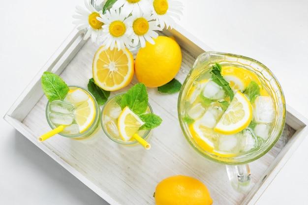 Dwie szklanki mglistego i karafka z domową lemoniadą na tacy. chłodzący napój w gorące lato. cytryny, mięta i lód. widok z góry.
