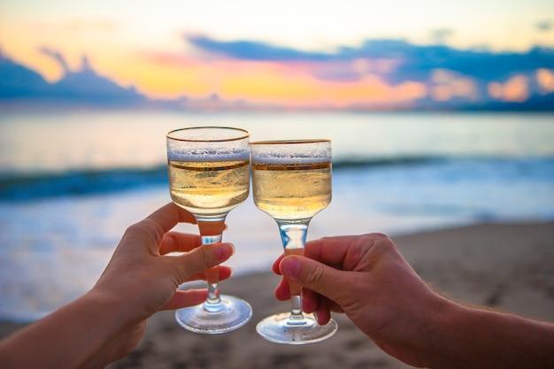 Dwie szklanki na białej, piaszczystej plaży