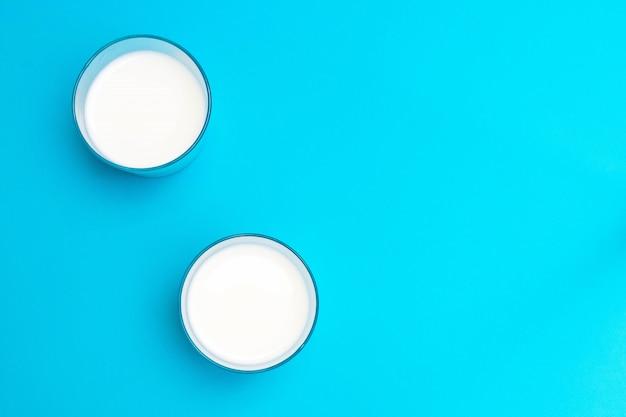 Dwie szklanki napoju na bazie jogurtu ayran (kefir) z solą i wodą na niebieskim stole.