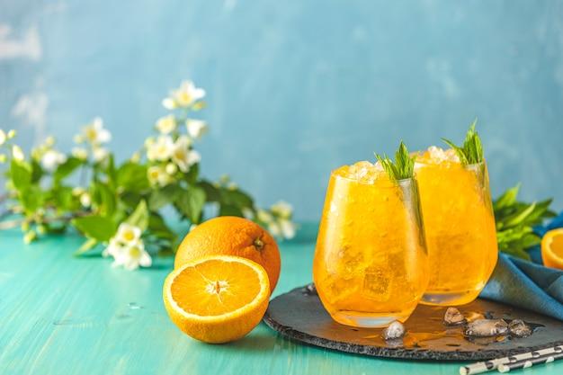 Dwie szklanki napoju pomarańczowego lodu ze świeżą miętą na drewnianej powierzchni stołu turkusowego