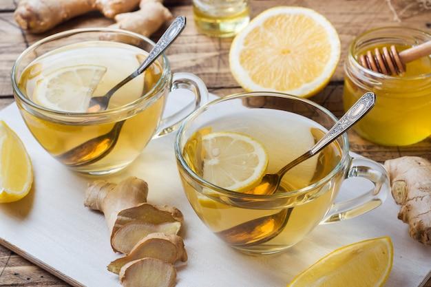Dwie szklanki naturalnej ziołowej herbaty imbirowej cytryny i miodu na drewnianej powierzchni.