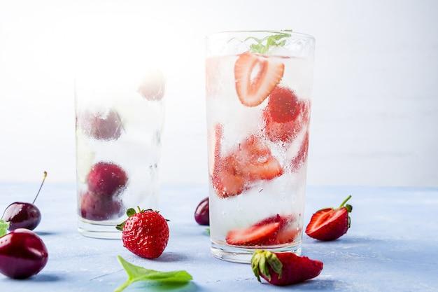 Dwie szklanki odświeżającego chłodnego napoju detox z truskawkami, wiśnią i miętą