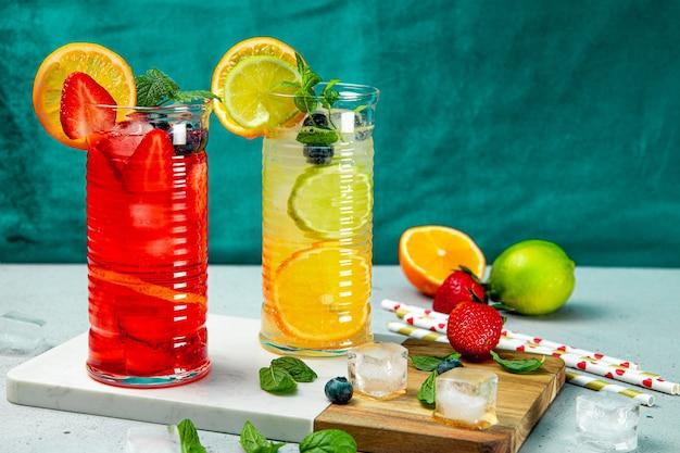 Dwie szklanki orzeźwiającej letniej lemoniady z lodem. koktajl z truskawką i cytryną oraz koktajl z cytryną i limonką