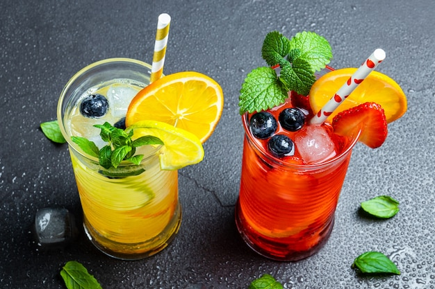 Dwie szklanki orzeźwiającej letniej lemoniady z lodowym koktajlem z truskawkami i cytryną oraz koktajl