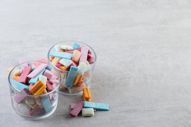 Dwie szklanki pełne z kolorowymi gumami na szarym tle.