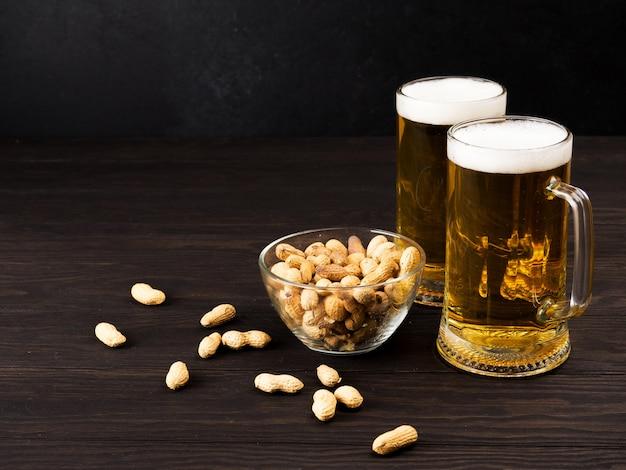 Dwie szklanki piwa i frytki i orzeszki ziemne na drewnianym ciemnym