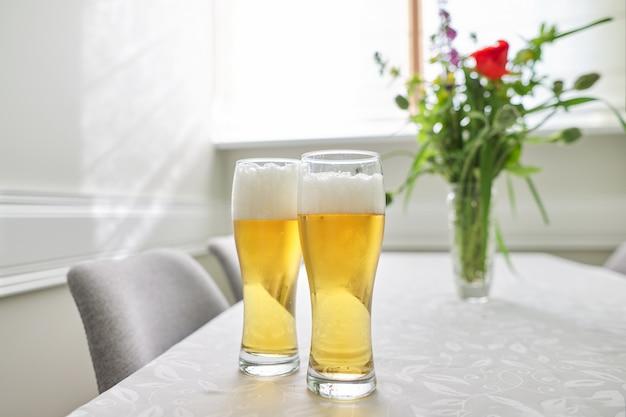 Dwie szklanki piwa na stole, stół domowy z krzesłami w pobliżu okna.