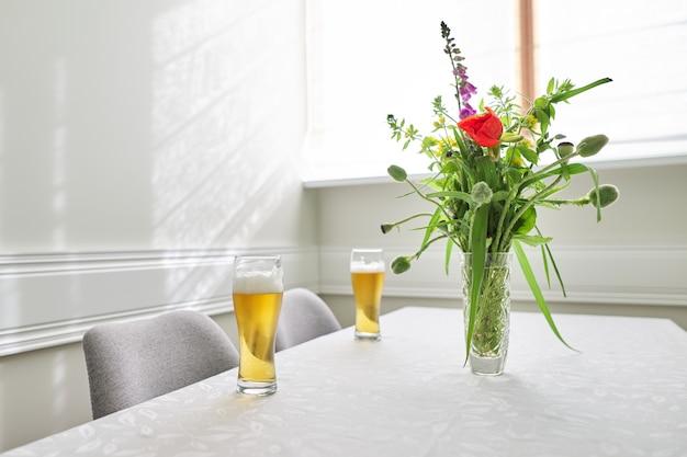 Dwie szklanki piwa na stole, stół domowy z krzesłami w pobliżu okna