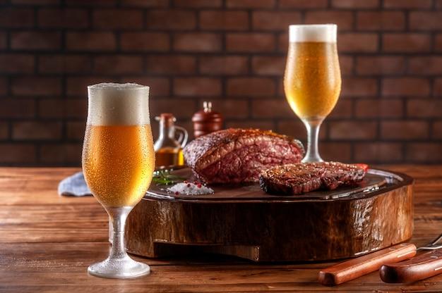 Dwie szklanki piwa spocony zimny tulipa z grillowanym pokrojonym stek rump cap na drewnianej desce do krojenia (brazylijska picanha).