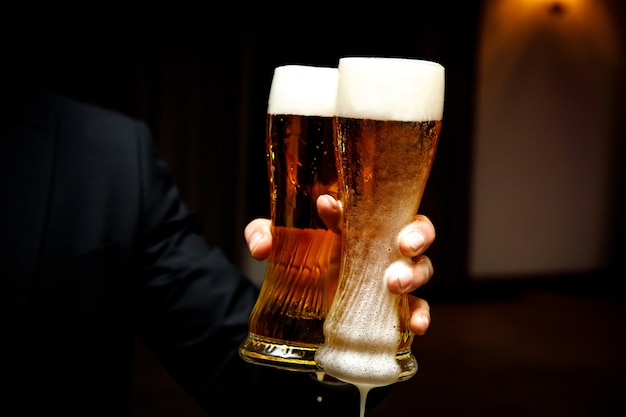 Dwie szklanki piwa z dużą ilością piany w rękach.