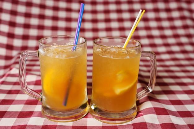 Dwie szklanki piwnych koktajli na kraciastej tkaninie
