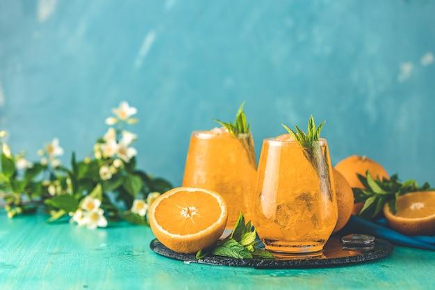 Dwie szklanki pomarańczowego lodu piją ze świeżą miętą na drewnianej powierzchni stołu turkusowego
