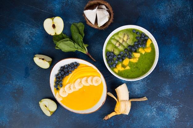 Dwie szklanki różnych misek smoothie z zielonymi i żółtymi owocami. pojęcie zdrowego odżywiania. poziome zdjęcie. widok z góry.