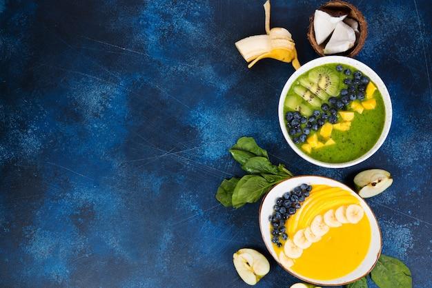 Dwie szklanki różnych misek smoothie z zielonymi i żółtymi owocami. pojęcie zdrowego odżywiania. poziome zdjęcie z miejsca kopiowania. widok z góry.