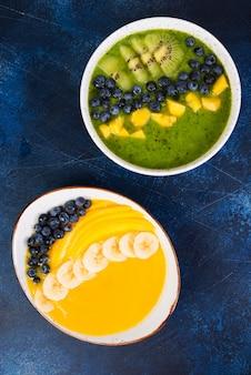 Dwie szklanki różnych misek smoothie z zielonymi i żółtymi owocami. pojęcie zdrowego odżywiania. zdjęcie pionowe. widok z góry.