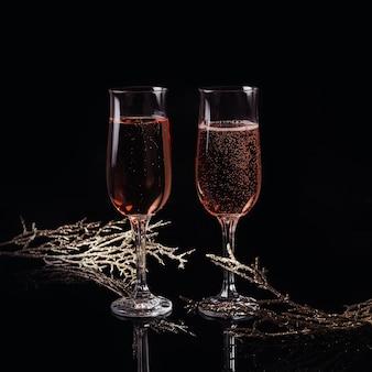 Dwie szklanki różowego szampana i dekoracji świątecznej lub noworocznej na czarnym tle. romantyczna kolacja. koncepcja zimowych wakacji.
