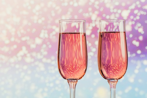 Dwie szklanki różowego szampana z lekkim śniegiem bokeh