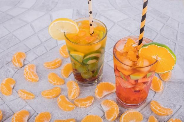 Dwie szklanki soku z kawałkami owoców na marmurowej powierzchni.