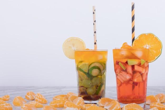 Dwie szklanki soku z kawałkami owoców.