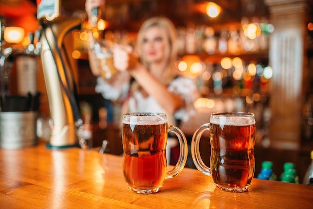 Dwie szklanki świeżego piwa na ladzie, seksowna kelnerka nalewa spieniony napój do kubka w pubie.