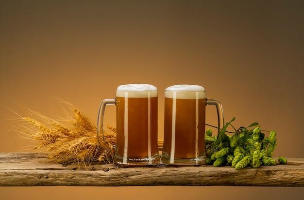 Dwie szklanki świeżego piwa z pianką, chmielem i pszenicą w pobliżu szklanek