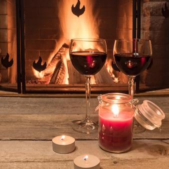 Dwie szklanki świń i świece przed przytulnym ogniem.