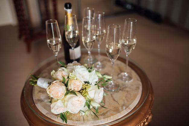 Dwie szklanki szampana i piękny ślubny bukiet jaskierów i białego bzu na białej, pomalowanej drewnianej desce