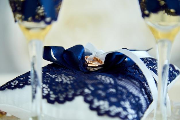 Dwie szklanki szampana i poduszka z obrączkami