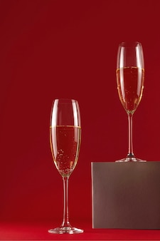 Dwie szklanki szampana na stojaku na czerwono