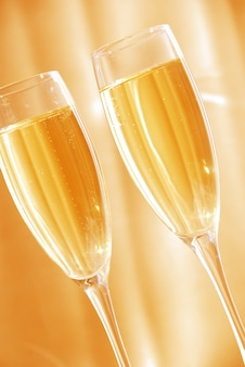 Dwie szklanki szampana na złotym tle
