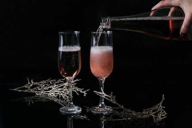 Dwie szklanki szampana różanego i dekoracji świątecznej lub noworocznej na czarno