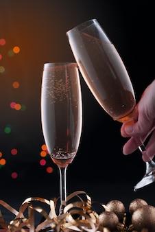 Dwie szklanki szampana ze świątecznymi światłami