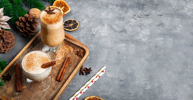 Dwie szklanki tradycyjnych ajerkoniak pić boże narodzenie na szarym tle, baner internetowy z miejsca kopiowania tekstu. pikantny napój z jajka i mleka z dodatkiem cynamonu, kardamonu. zdjęcie wysokiej jakości
