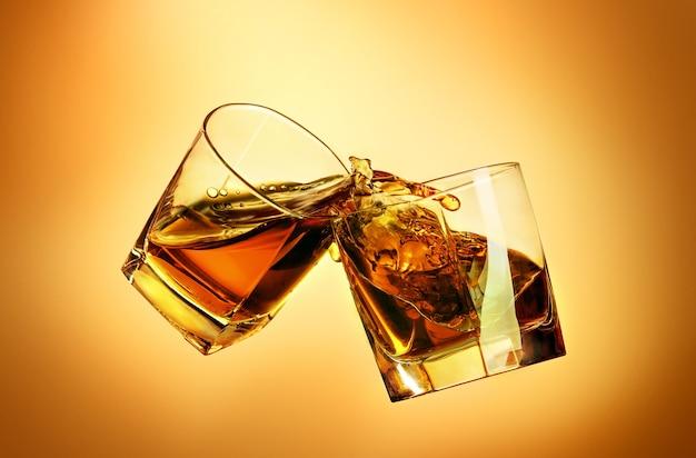 Dwie szklanki whisky brzęczące o siebie na brązowym tle studyjnym