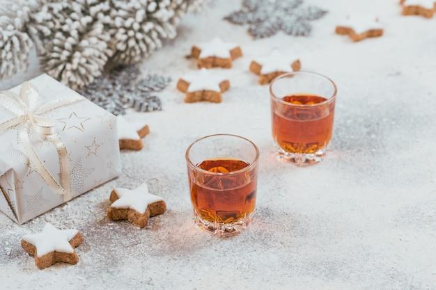 Dwie szklanki whisky lub bourbon, ciasteczka gwiazdki i ozdoba na białym tle. koncepcja zimowego nastroju whisky