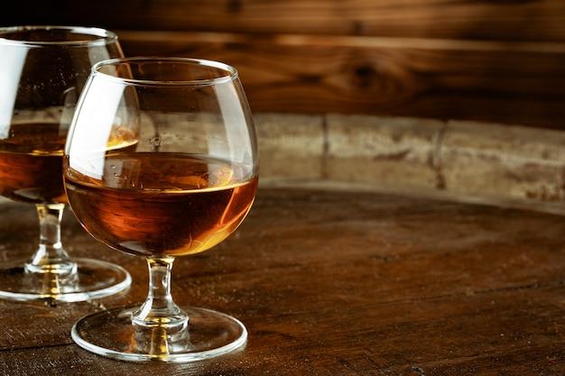 Dwie szklanki whisky na drewnianym stole w barze