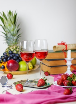 Dwie szklanki wina różanego na białym drewnianym stole z zabytkowymi książkami i zegarem, różnymi owocami tropikalnymi i truskawkami