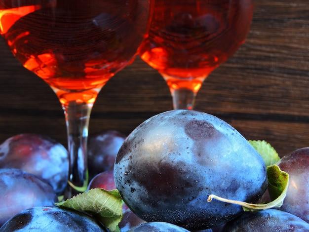 Dwie szklanki wina śliwkowego. jasne niebieskie śliwki na ciemnym drewnianym.