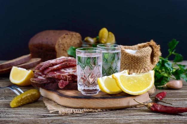 Dwie szklanki wódki z plasterkiem cytryny, kiszone ogórki i chleb żytni z solonym boczkiem na ciemnym tle.