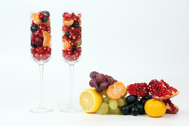 Dwie szklanki wypełnione owocami na świetle