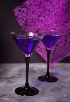 Dwie szklanki z fioletowym koktajlem na imprezę halloween w ciemności