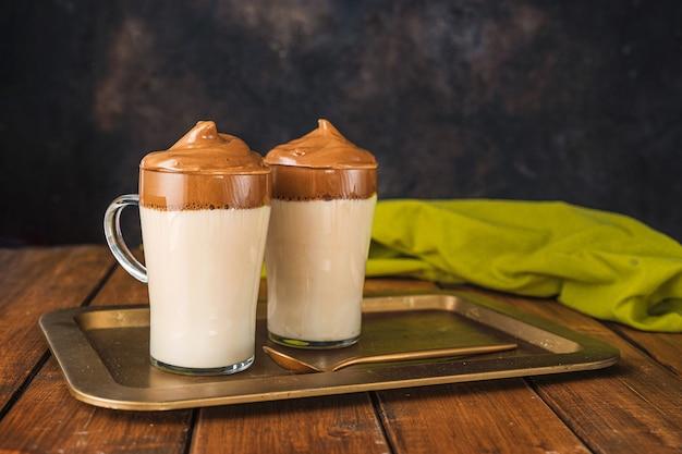 Dwie szklanki z modną kawą dalgona wykonaną z bitej kawy rozpuszczalnej z wodą i cukrem