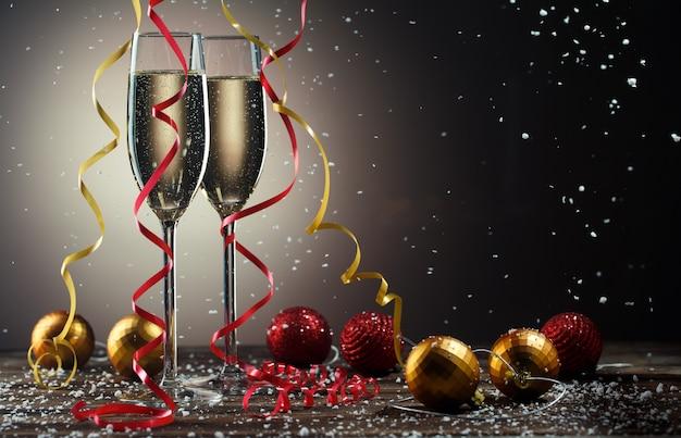 Dwie szklanki z musującym szampanem, płatki śniegu i świąteczna czerwono-żółta kulka ze wstążkami.