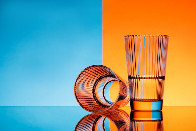 Dwie szklanki z wodą na niebieskim i pomarańczowym tle.