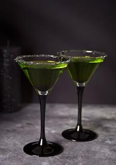 Dwie szklanki z zielonym koktajlem zombie na przyjęcie halloween na szarym tle