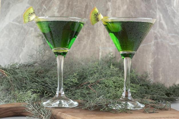 Dwie szklanki zielonego koktajlu z plasterkami kiwi na desce.