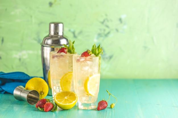 Dwie szklanki zimnego lodowego orzeźwiającego napoju z cytryną i truskawką podawane z barem narzędzi na zielonym drewnianym stole.