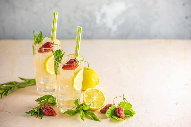 Dwie szklanki zimnego lodowego orzeźwiającego napoju z cytryną i truskawką